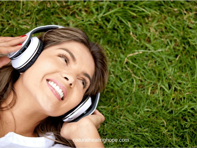 How to Start Listening to Your Body to Restore Your Health: Woman listening to earphones laying on the grass, looking happy