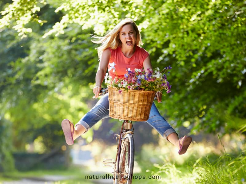 Lady having a blast on a bike full of a basket of flowers living her best summer ever.