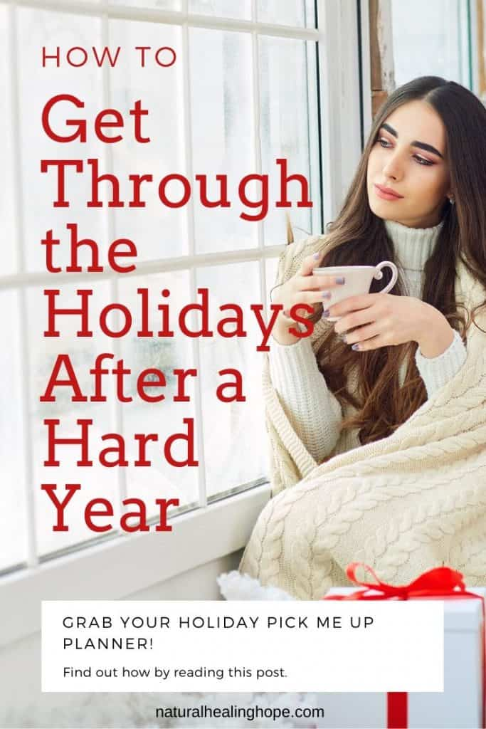 A lady drinking tea looking out the window in a reflective way with text overlay that says: How to get through the Holidays after a hard year.