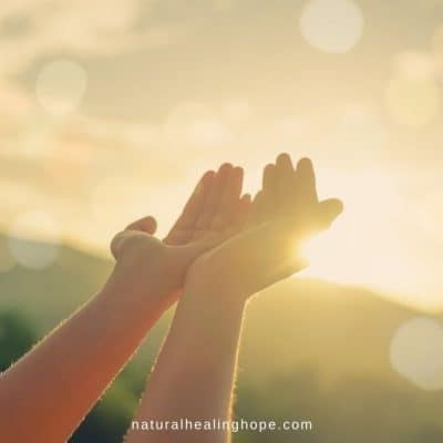 Picture of receptive hands being lifted up to the sunset to receive the blessing.
