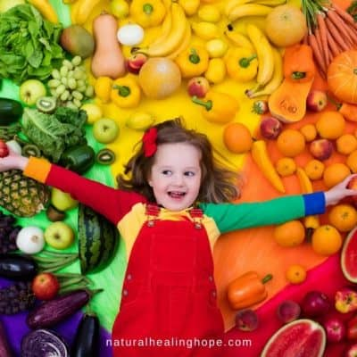 A Healthy Child with arms outstretched holding apples and laying on a pile of fruits and vegetables by color, to go with post about Juice Plus Health Made Simple Solutions.