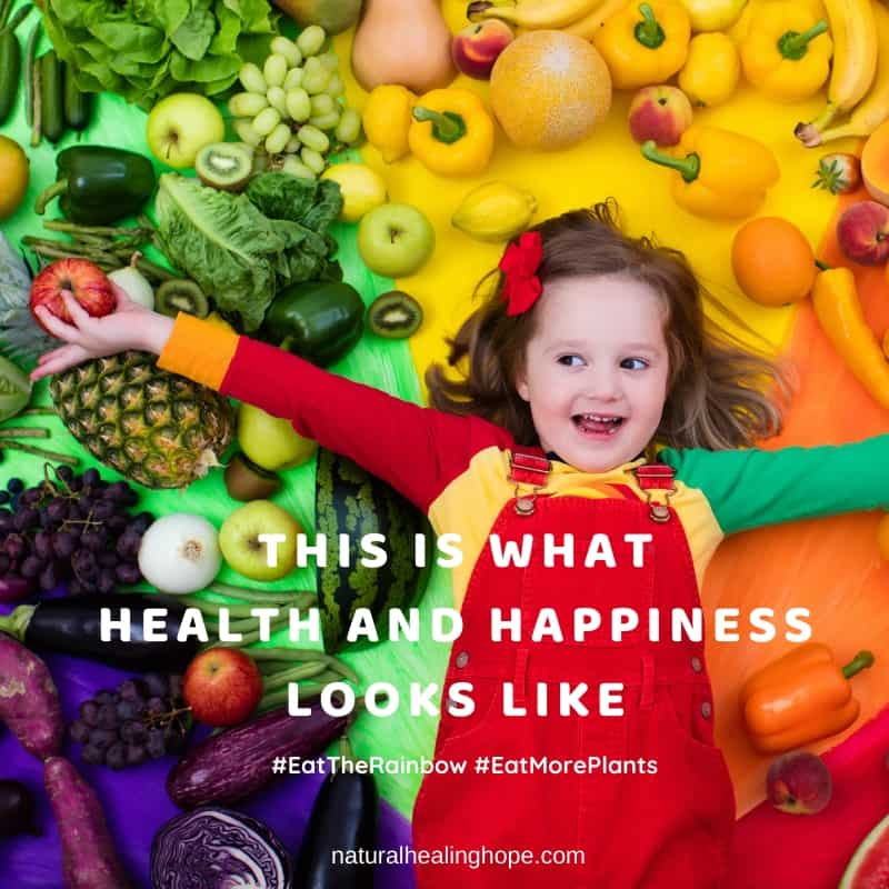 "Happy little girl with arms outstretched, holding an apple, laying on a pile of fruits and vegetables spread out according to color. Text overlay says, ""This is what health and happiness looks like. #EatTheRainbow #EatMorePlants"""