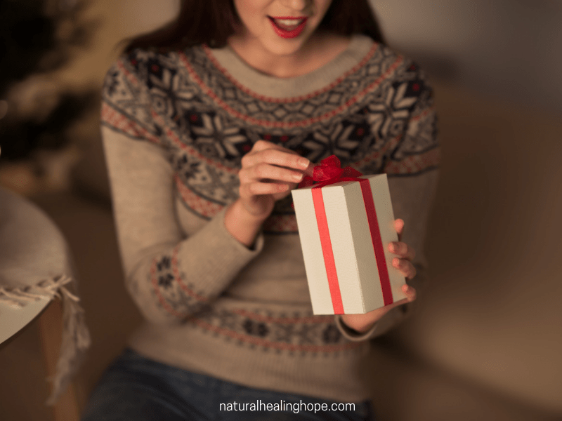 happy lady unwrapping a gift- better health by christmas challenge
