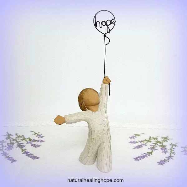 figurine holding onto a balloon that says hope