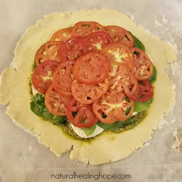 adding tomatoes to the rustic heirloom tomato galette